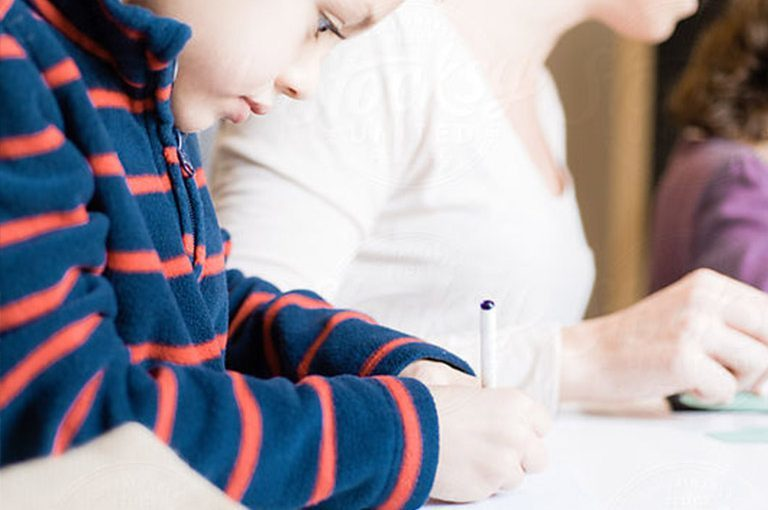 boy using pen to write on paper