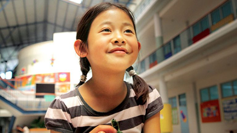 young Asian girl smiling and looking up