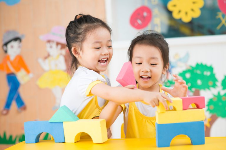 Two girls playing with blocks.